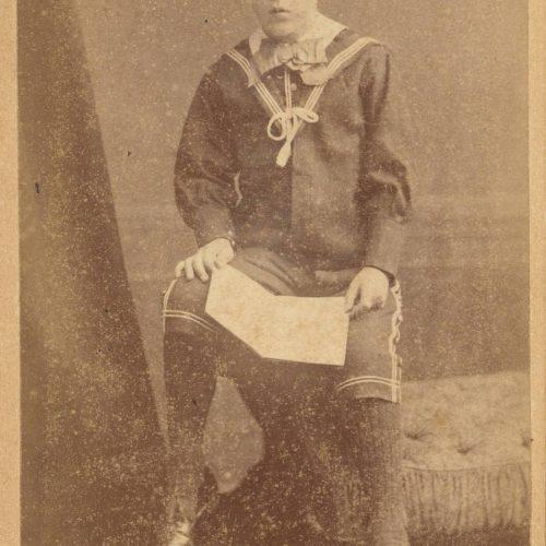 Φωτογραφία αγοριού με ναυτική ενδυμασία, που κάθεται στο μπράτσο κα�