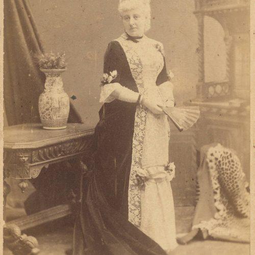 Φωτογραφία γυναίκας που στέκεται δίπλα σε τραπέζι. Φοράει μακρύ φόρ�