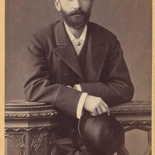Φωτογραφία άνδρα με κοστούμι, που κρατάει καπέλο στο δεξί χέρι. Ο λογ