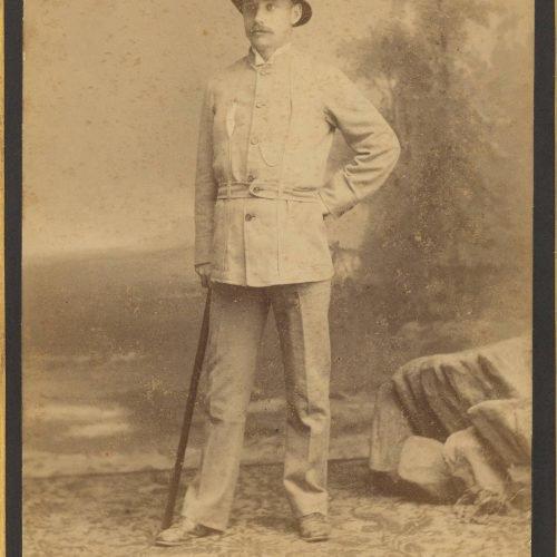 Φωτογραφία όρθιου άνδρα με αποικιακή αμφίεση και αποικιακό καπέλο. �